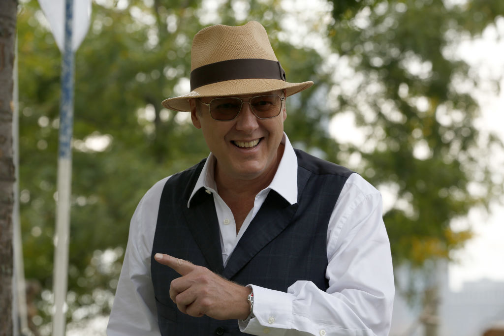 James Spader as Raymond 'Red' Reddington  smiles for the camera. He's wearing a tan fedora, dark gray vest, sunglasses, and a long-sleeve white shirt.