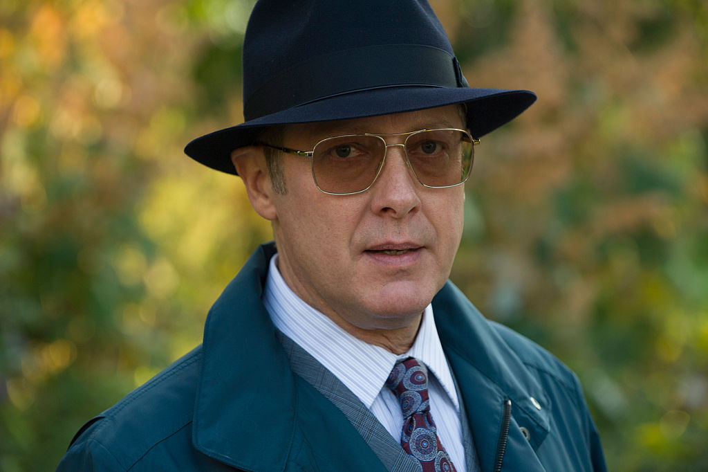 James Spader as Raymond 'Red' Reddington is dressed in a navy trench coat, matching fedora, and sunglasses as he looks directly into the camera for a close-up shot.