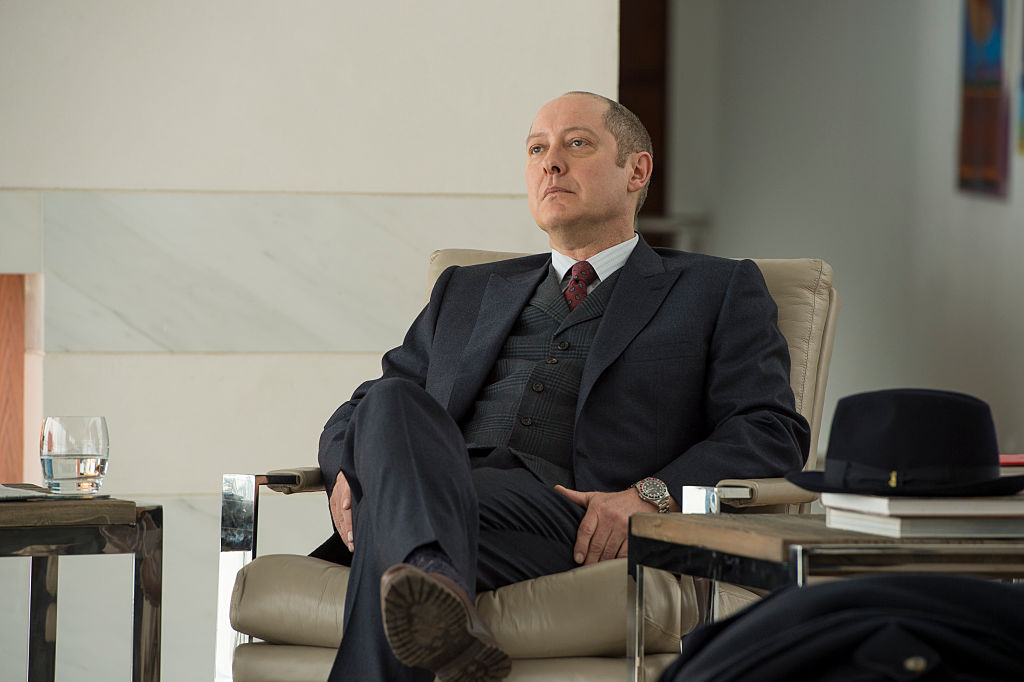 James Spader as Raymond 'Red' Reddington is dressed in a dark suit as he sits in a chair, unimpressed.
