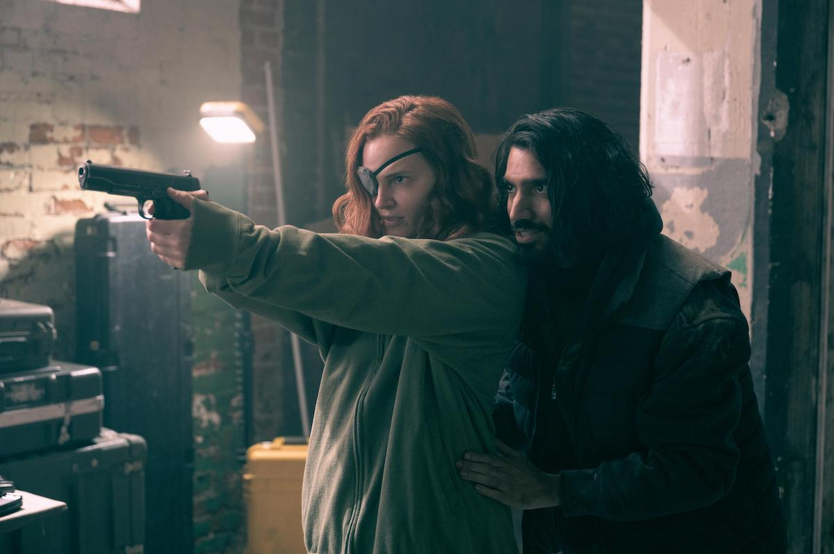Madeline Brewer and Omar Maskati as Janine and Steven in 'The Handmaid's Tale' Season 4. In the photo, Brewer wears a grey zip-up hoodie and a beanie and an eyepatch as she points a gun. Maskati stands behind her, his hands on her waist. He wears a jacket with a vest over it. They're in a dilapidated warehouse where the Chicago resistance against Gilead hides. In 'The Handmaid's Tale' Season 4, Janine's backstory was revealed. Brewer says Janine's backstory is in the back of her mind in every scene she does in the Hulu series.