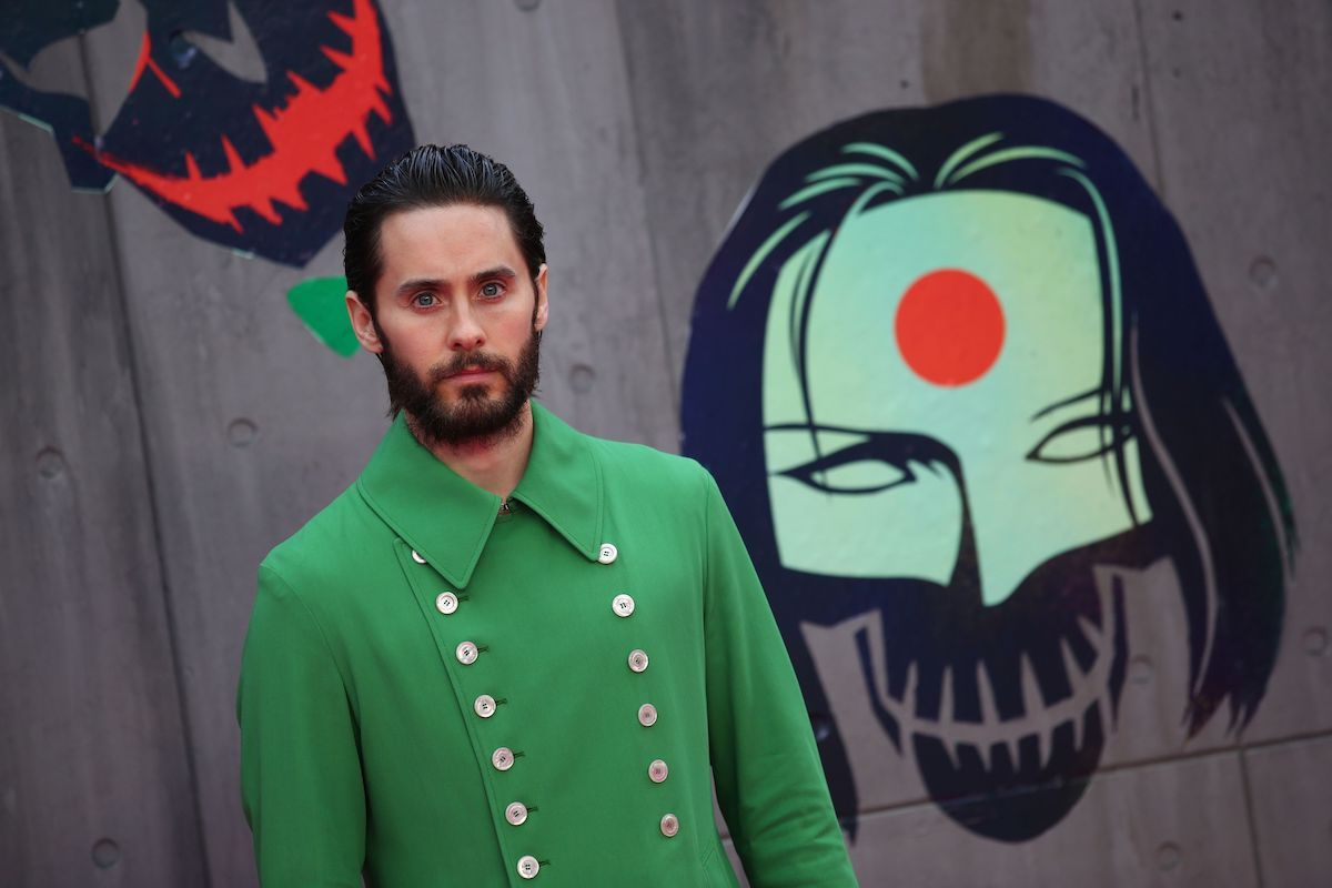 Jared Leto poses in a suit in front of 'Suicide Squad' artwork