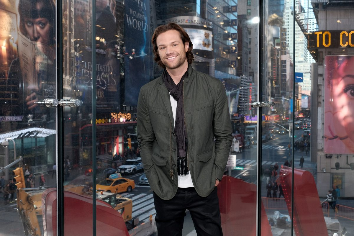 Jared Padalecki smiling in front of Times Square window