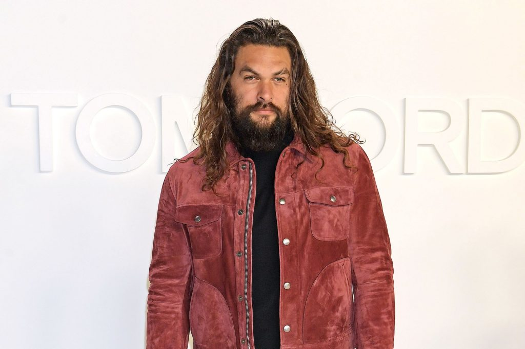 Jason Momoa dressed in a redish brown jacket with a black shirt and pants in front of a white background.
