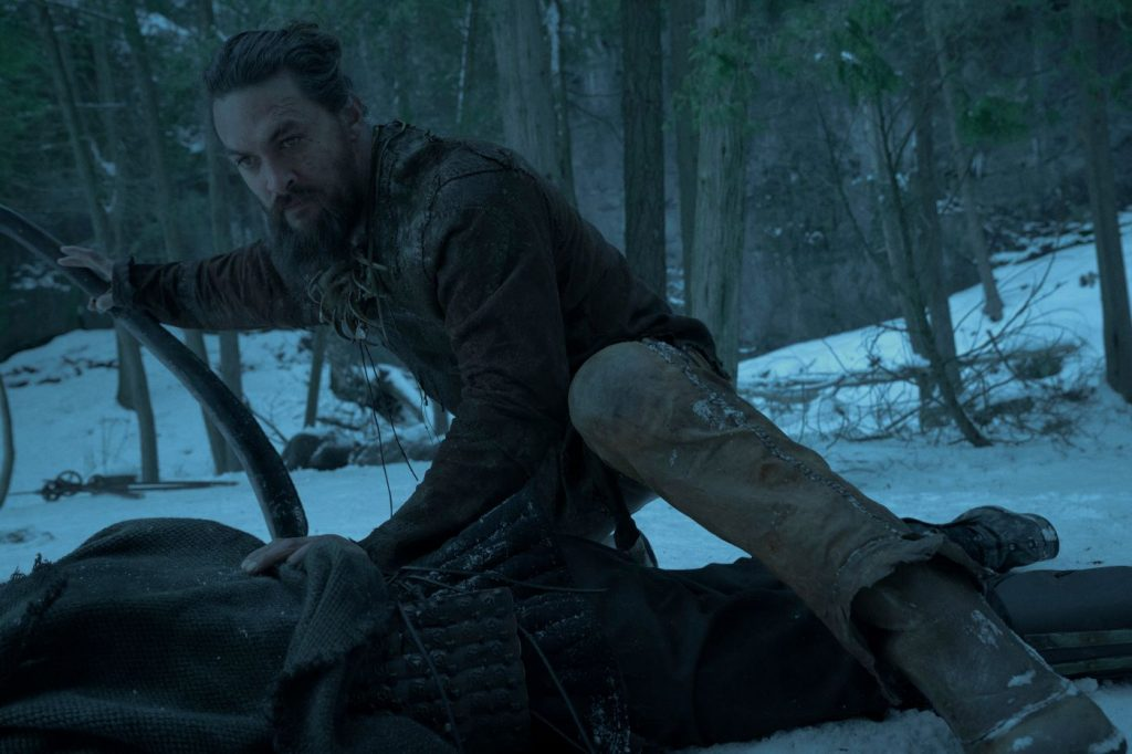 Jason Momoa crouches in the snow during a scene in the show 'See.'