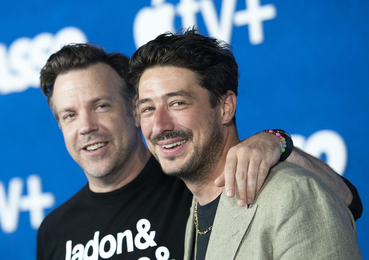 Jason Sudeikis (L) and Marcus Mumford (R) at the 'Ted Lasso' Season 2 premiere on July 15, 2021. Sudeikis wears a black long-sleeved shirt with white writing and Mumford wears a beige suit jacket. They stand in front of a blue backdrop. Sudeikis has his left arm around Mumford's shoulder.