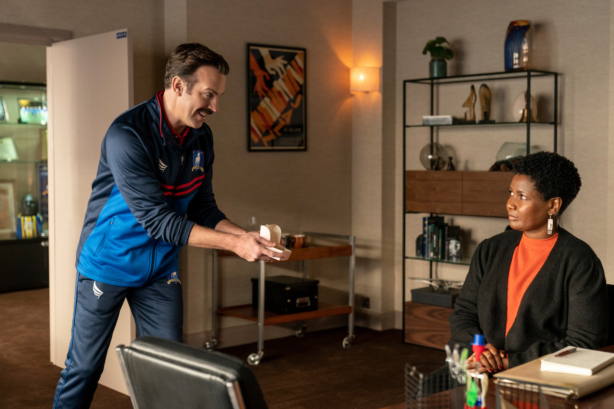 Jason Sudeikis wears a blue jacket as he offers a pink box of biscuits to a seated Sarah Niles in 'Ted Lasso' Season 2