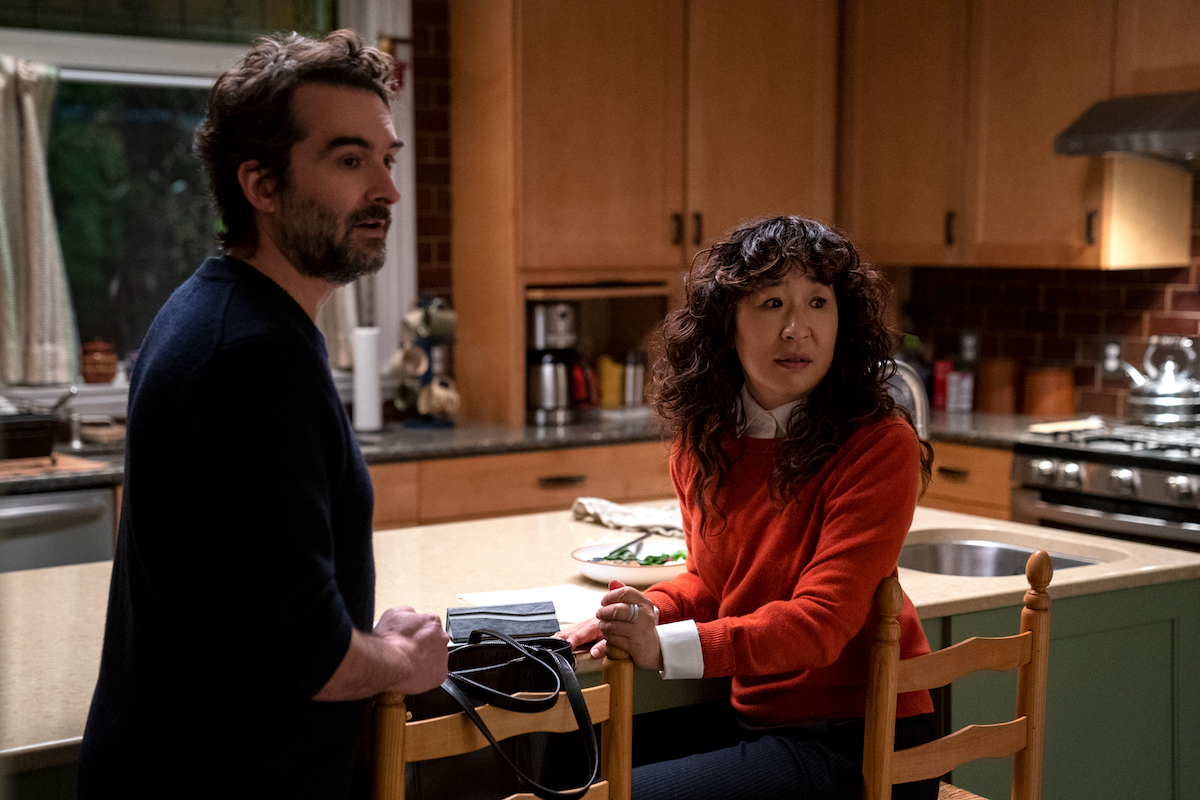Jay Duplass and Sandra Oh stand at a kitchen island and look on in 'The Chair' Season 1 Episode 4