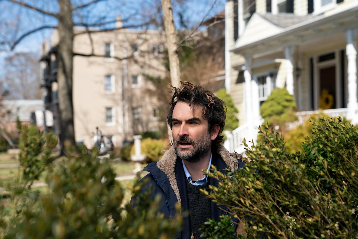 Jay Duplass stands in bushes with leaves in his hair as Bill Dobson in 'The Chair' Season 1