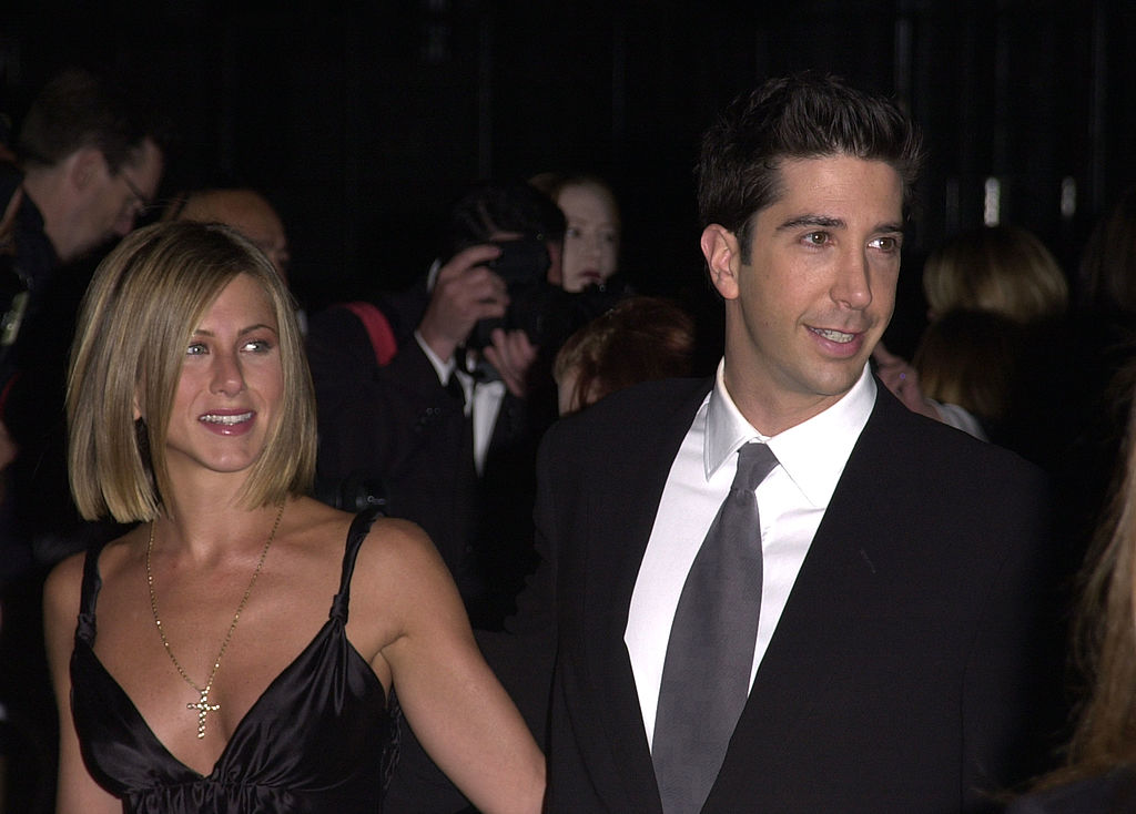 Jennifer Aniston and David Schwimmer attend an awards party. Aniston is dressed in a black spaghetti strap dress and Schwimmer is wearing a black suit, white shit, and tie.