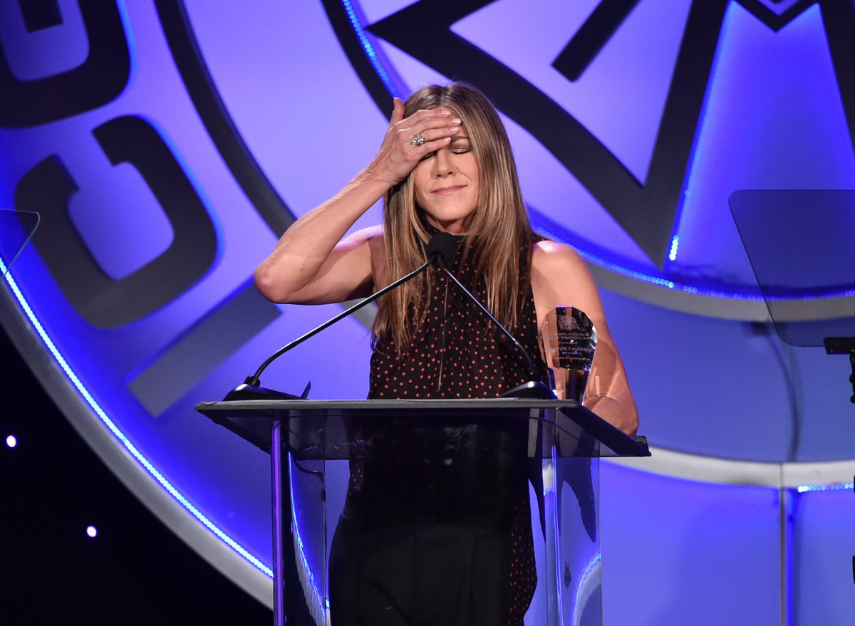 Jennifer Aniston puts her hand on her forehead