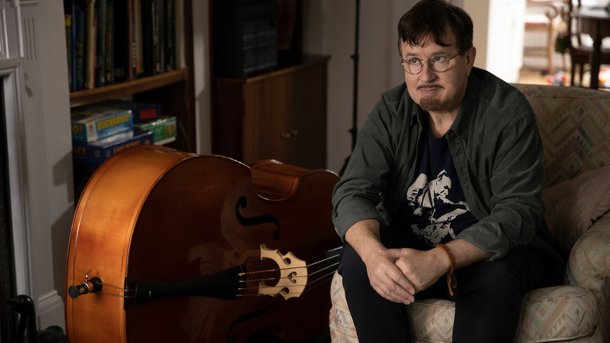 Jeremy Swift sits on a chair next to a double bass as Leslie Higgins in 'Ted Lasso'