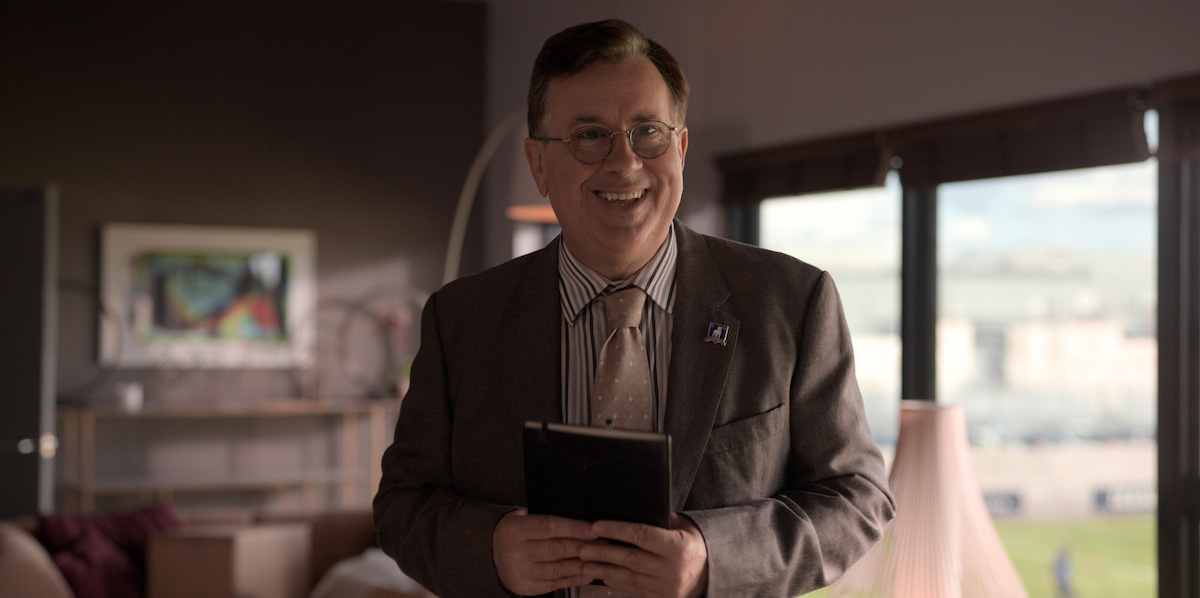 Jeremy Swift smiles wearing a suit and tie while holding a notebook as Leslie Higgins in 'Ted Lasso'