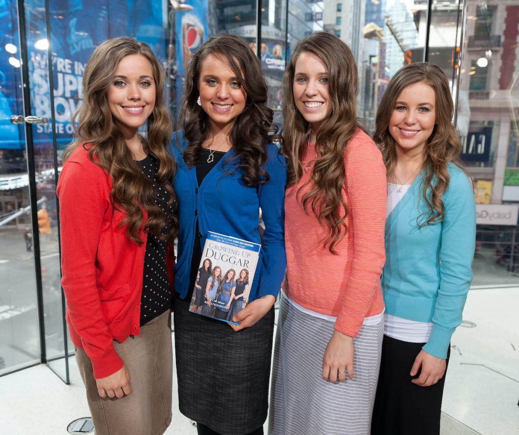 """Jessa, Jinger, Jill, and Jana pose with their book, """"Growing Up Duggar,"""" in 2014"""