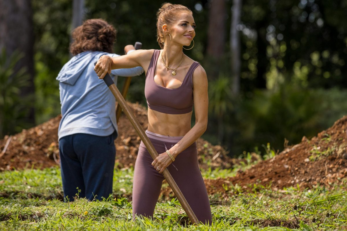 Jessica smiling and digging with a shovel, wearing a purple sports bra and leggings.