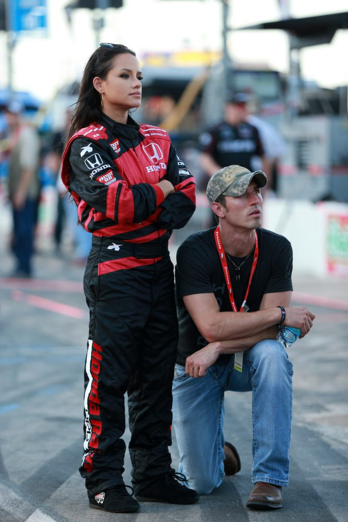 Jessica Graf stands in racing attire, looking off into the distance, while husband Cody Nickson kneels by her side.