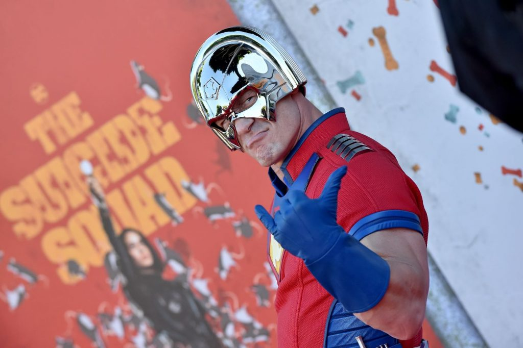 John Cena dressed as a DC superhero, Peacemaker, standing in front of a background of a Suicide Squad poster with confetti.