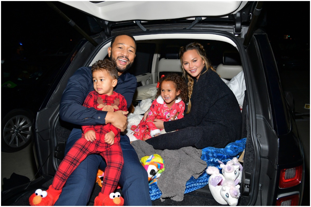 Chrissy Teigen, John Legend, and their children Miles and Luna sitting in the trunk of a car in pajamas.