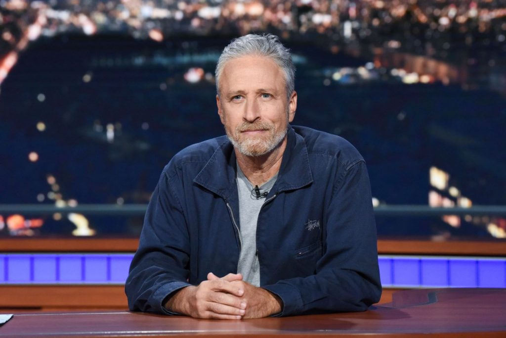 Jon Stewart sitting behind a desk with a city in the background wearing a grey shirt with a blue jacket.