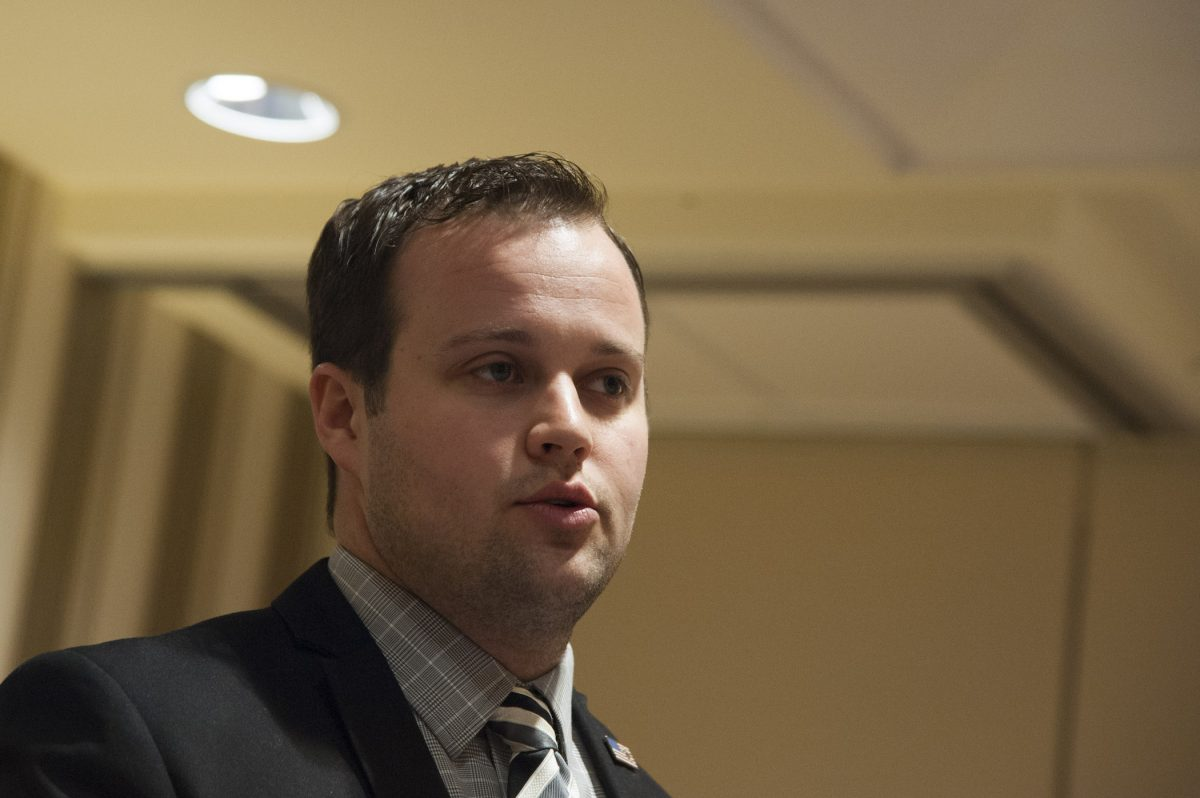 Josh Duggar of the Duggar family half in the shadows at a conference