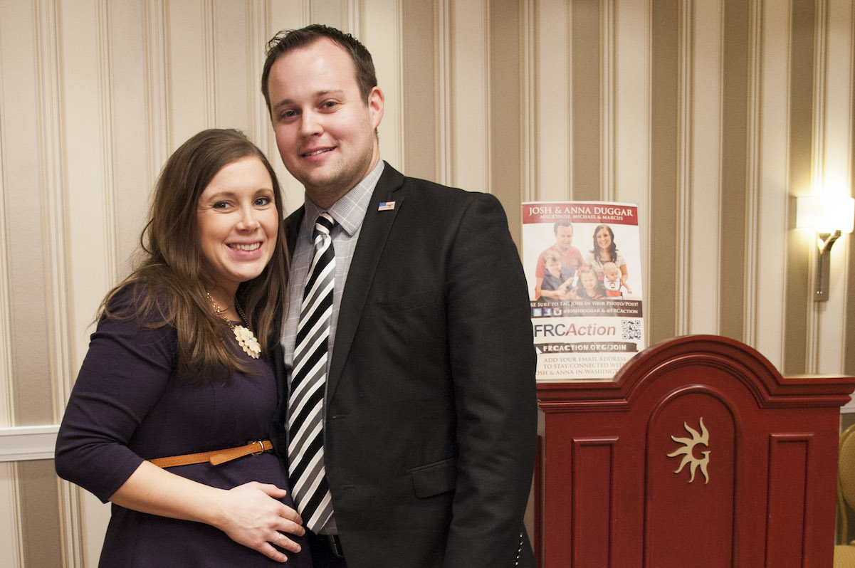 Anna Duggar wearing a blue dress posing for a photo with her husband Josh Duggar wearing a suit and tie.