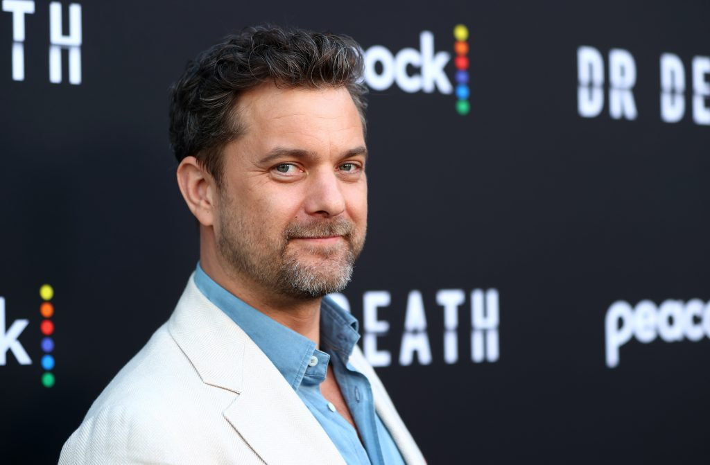 Joshua Jackson smiling in front of a black background