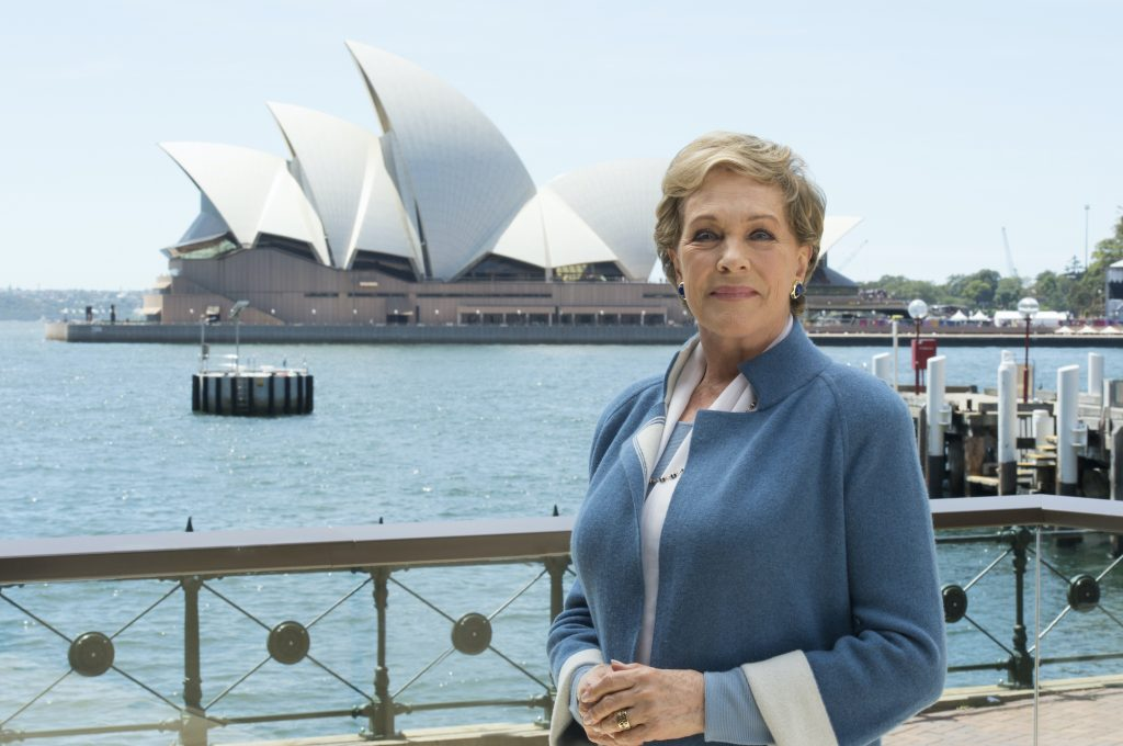 Julie Andrews smiling in front of the Sydney Opera House