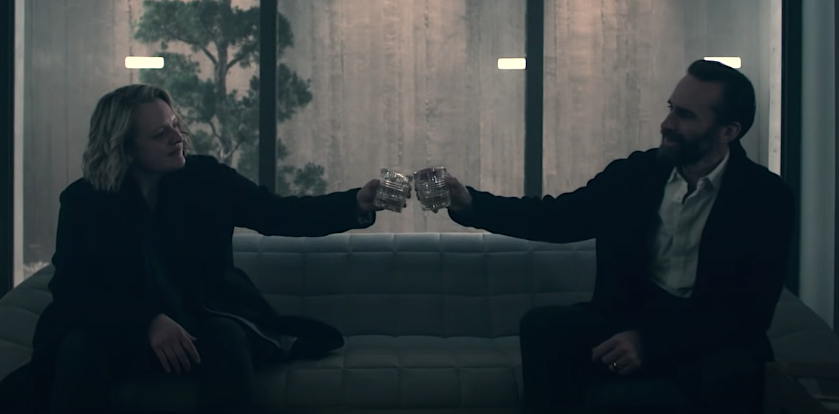 Elisabeth Moss and Joseph Fiennes as June and Fred in 'The Handmaid's Tale' Season 4 Episode 10, 'The Wilderness.' Liz Garbus directed the Emmy-nominated episode, which shows June and Fred's final scenes together. Moss and Fiennes sit on a couch in a high-end prison cell. Floor-to-ceiling windows are behind them as they hold their glasses up in cheers to Ofred, the name June was called when she was forced to live in Fred and Serena's house.