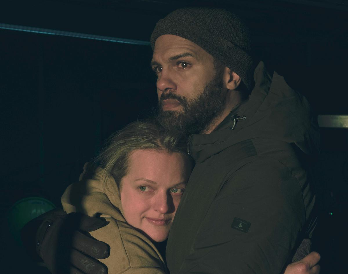 Elisabeth Moss and O-T Fagbenle as June and Luke in 'The Handmaid's Tale' Season 4 Episode 6. It's night and they're hugging on a boat, the background isn't seen because of the lighting. Moss wears a yellow hoodie, Fagbenle wears a green winter coat, gloves, and a beanie. Moss has a slight smile on her face and Fagbenle looks relieved. This scene is much different than Luke and June's last scene in 'The Handmaid's Tale' Season 4 finale.