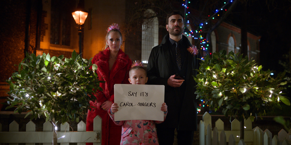 Juno Temple and Brett Goldstein stand between Elodie Blomfield as she holds up a poster board with writing on it in 'Ted Lasso' Season 2