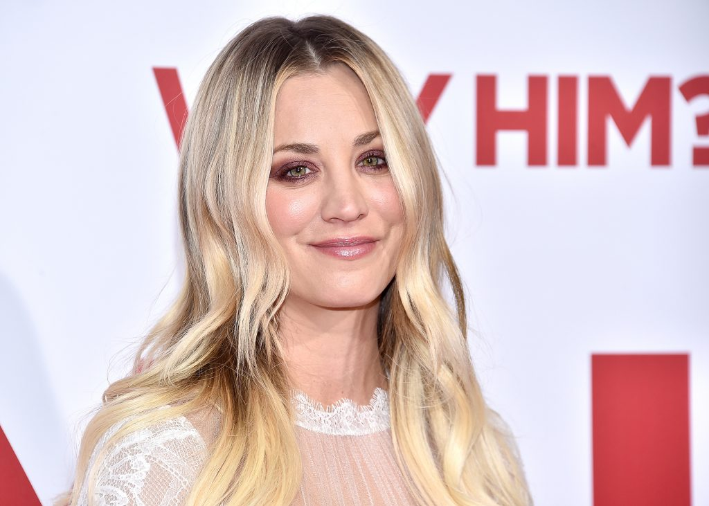 Kaley Cuoco smiles for a photo wearing white mesh top with hair down and parted in the middle
