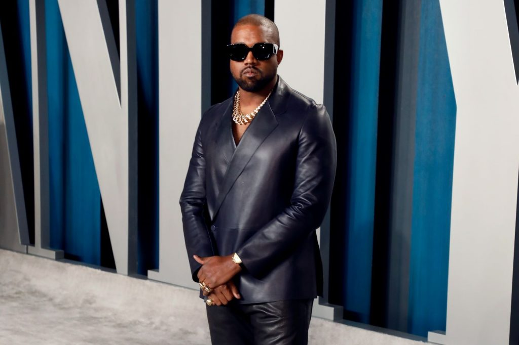 Kanye West dressed in a shiny black suit in front of a blue and white background.