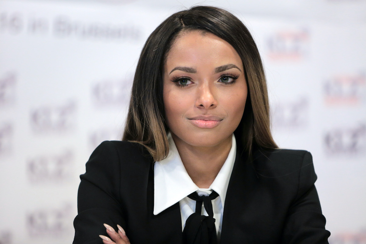 'The Vampire Diaries' star Kat Graham, who played Bonnie Bennett. Graham sits at a table in front of a white backdrop with blurred text that reads 'KLZ.' She was joined at the press conference by other 'The Vampire Diaries' cast members, like Michael Malarkey, who played Bonnie Bennett's boyfriend, Enzo. Creator Julie Plec says Bonnie Bennett's 'The Vampire Diaries' ending was going to show her married to someone other than Enzo.