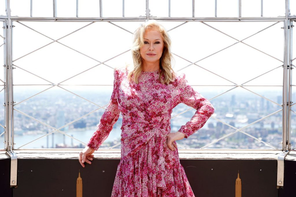 Kathy Hilton stands in front of a view of a city landscape wearing a long sleeve pink floral dress.