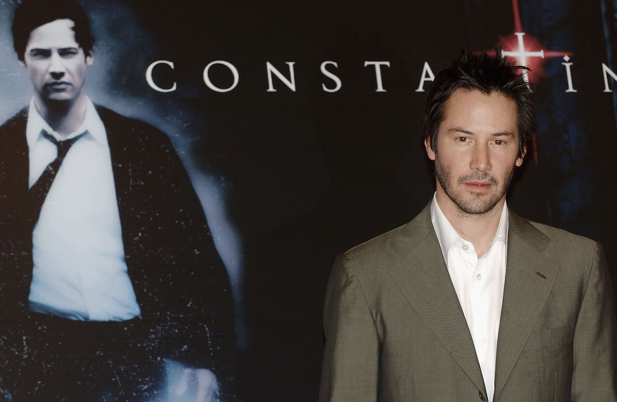 Keanu Reeves standing in front of 'Constantine' poster