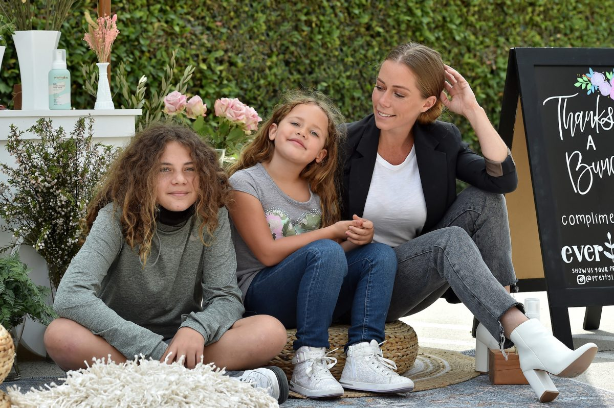 Kendra Wilkinson sits with her children