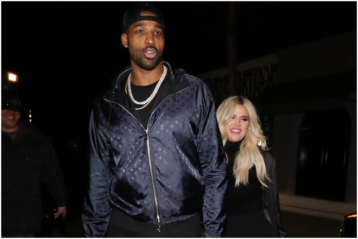 Khloé Kardashian and Tristan Thompson smiling and walking together during a night out.