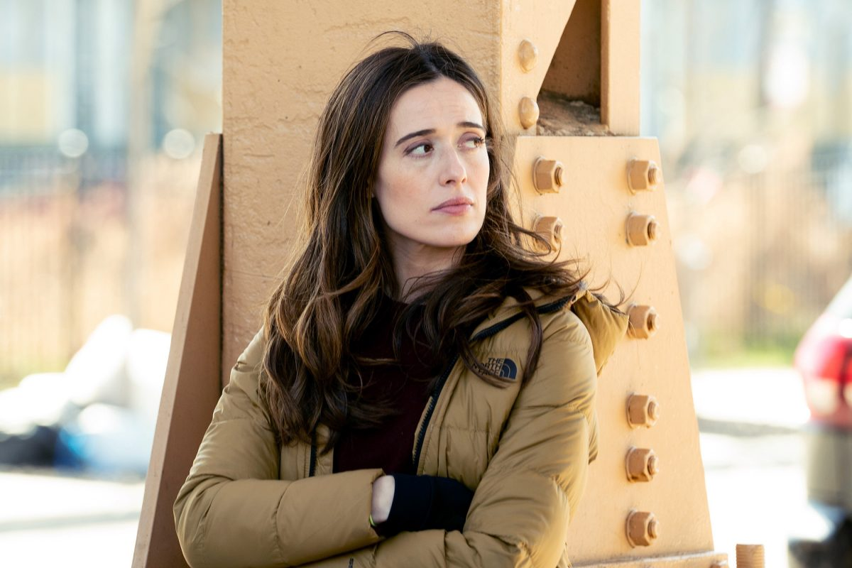 Marina Squerciati as Kim Burgess, a star in 'Chicago P.D.' Season 9, with her arms crossed leaning against a structure