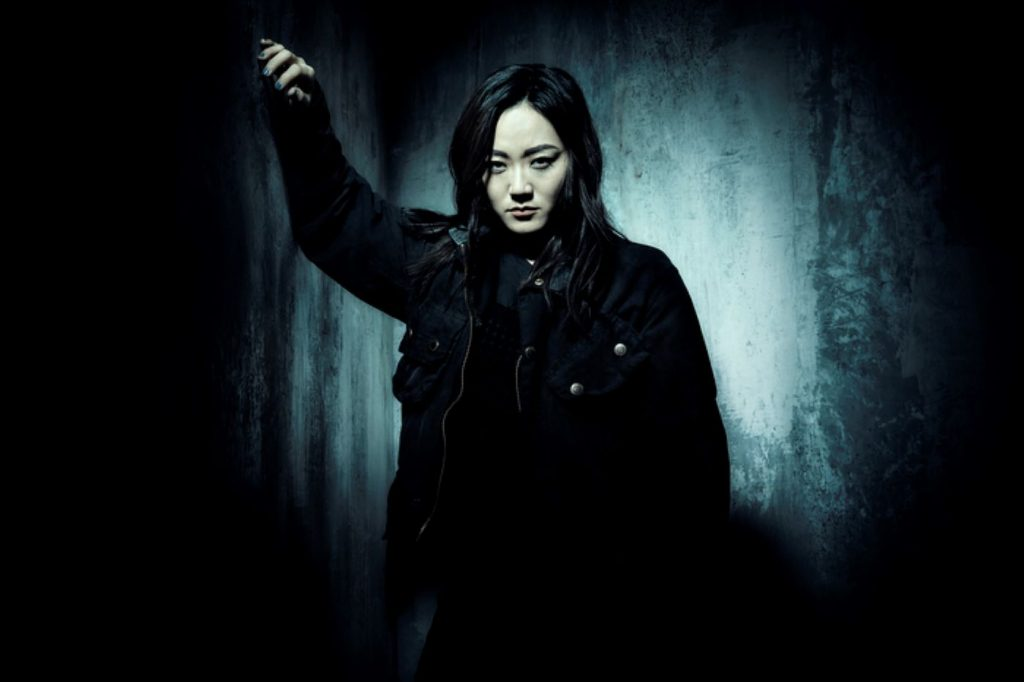 Kimiko from 'The Boys' is wearing a black jacket and pants against a drastic vignette with a grey center.
