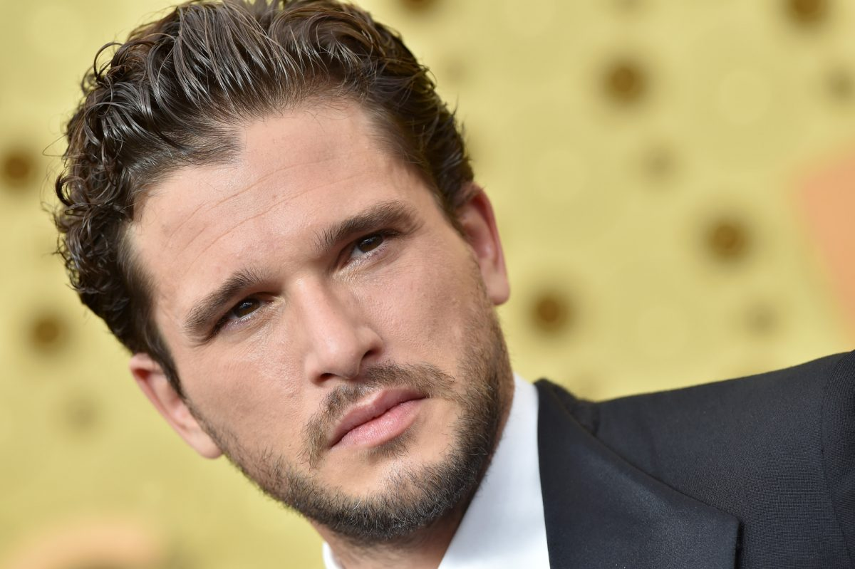 Game of Thrones star Kit Harington wearing a suit and standing in front of a golden wall