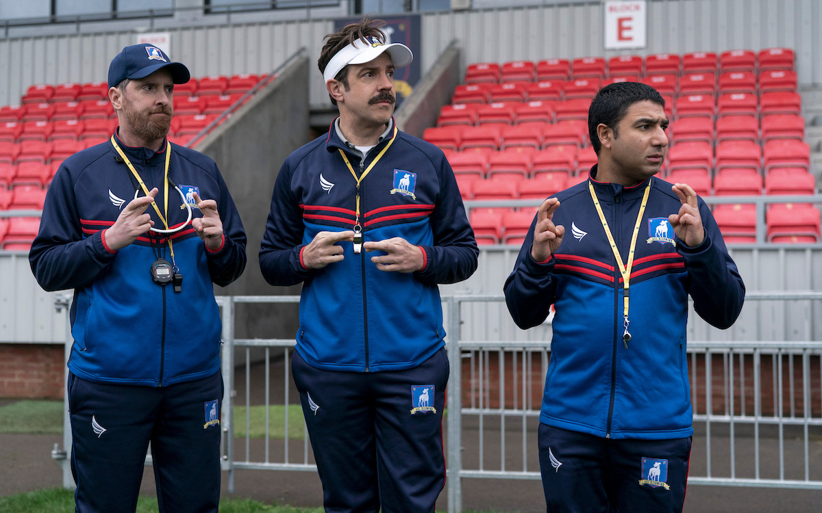 Brendan Hunt, Jason Sudeikis, and Nick Mohammed cross their fingers on 'Ted Lasso'