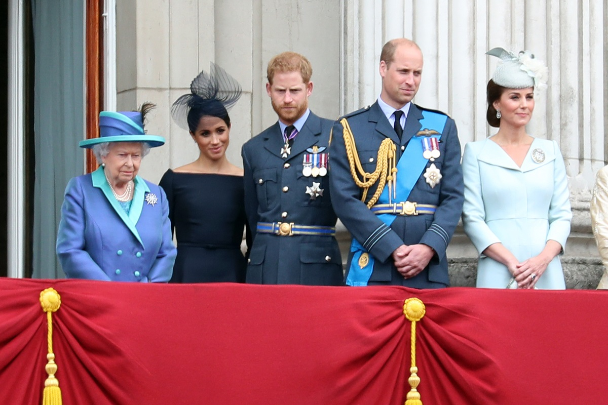 (L-R) Queen Elizabeth II, Meghan Markle, Prince Harry, Prince William, and Kate Middleton standing on the balcony of Buckingham Palace to watch a flypast