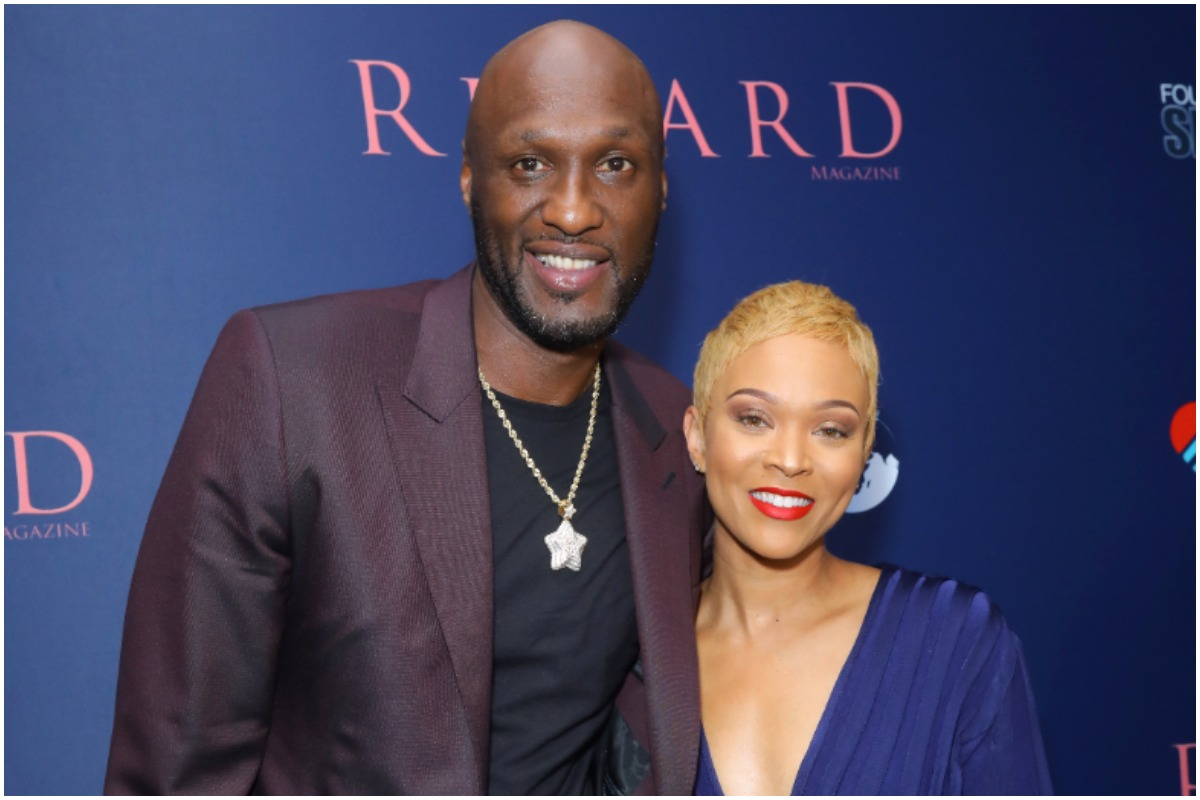 Lamar Odom and Sabrina Parr smiling and posing for the camera at an event.