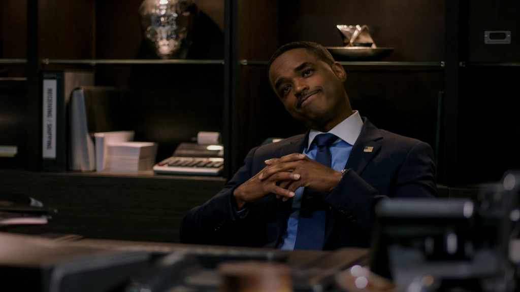 Larenz Tate sits behind a desk and claps his hands while wearing a suit as Rashad Tate in 'Power