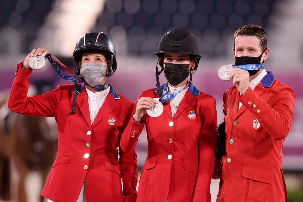 Laura Kraut, Jessica Springsteen and McLain Ward hold up their silver medals wearing equestrian gear and face masks
