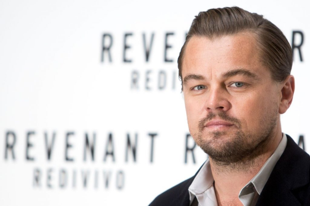 Leonardo DiCaprio, star of the revenant, dressed in a suit jacket and a collared shirt standing in front of a white background with Revenant written in black text.