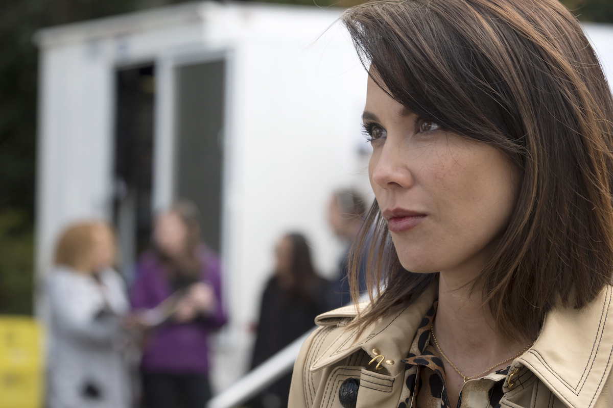 Lexa Doig in a trench coat looking off to the distance.