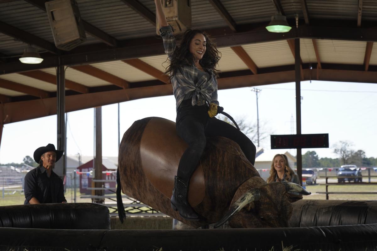 Lindsey Morgan rides a mechanical bull