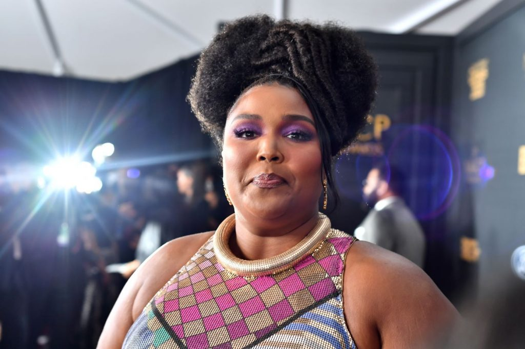 Lizzo is wearing a colorfully patterned top standing in front of a black background with gold writing and a bright light on the left side.