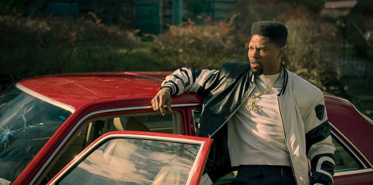 London Brown as Marvin leaning against his red Mercedes Benz in 'Power Book III: Raising Kanan'