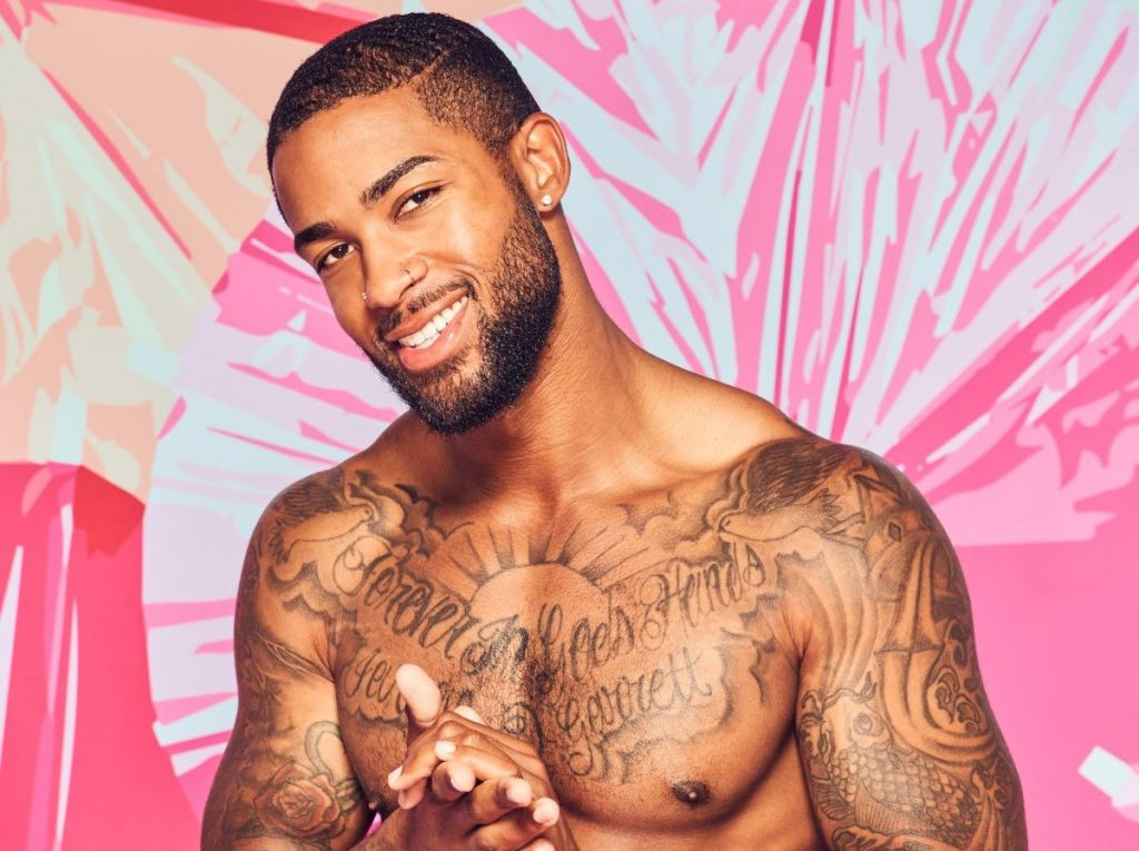 Charlie Lynch of 'Love Island' is shirtless and smiling rubbing his hands together.